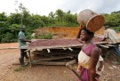 A woman walks past men working with cocoa beans in Enchi June 17, 2014. Picture taken June 17, 2014. To match Insight GHANA-IVORYCOAST/COCOA        REUTERS/Thierry Gouegnon (GHANA - Tags: AGRICULTURE BUSINESS FOOD) - GM1EA7S1OIZ01